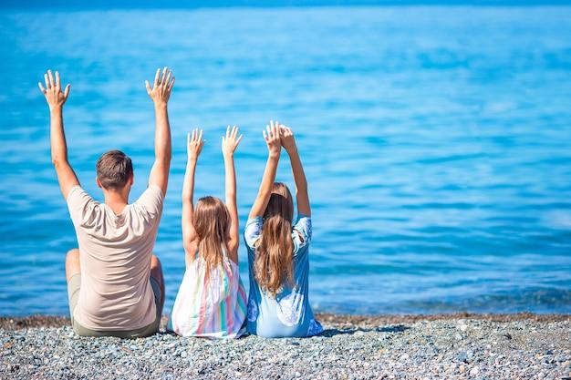 Vader en kleine meisjes op het strand hebben plezier op zomervakantie