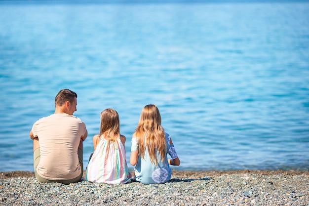 Vader en kleine meisjes op het strand hebben plezier tijdens de zomervakantie