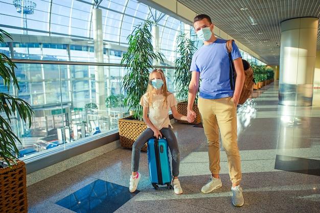 Vader en meisje met medische maskers op de luchthaven. bescherming tegen coronavirus en gripp