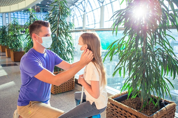 Vader en meisje met medische maskers op de luchthaven. bescherming tegen coronavirus