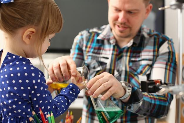 Vader en meisje spelen met kleurrijke vloeistoffen
