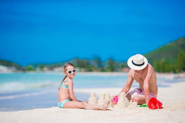 Vader en meisje spelen met zand op tropisch strand