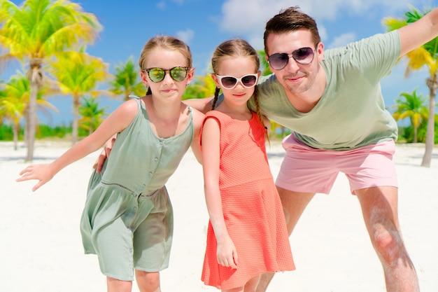 Vader en meisjes die pret op wit strand in palmbosje hebben
