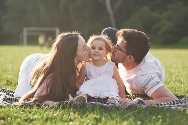 Vader en moeder brengen samen gelukkig tijd door. dochtertje speelt met haar ouders buiten tijdens zonsondergang