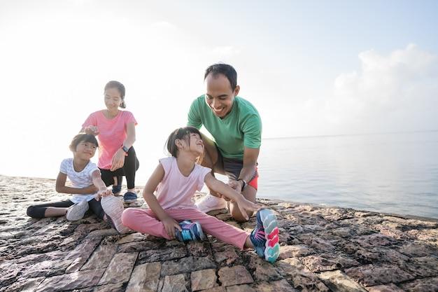 Vader en moeder helpen hun dochter om het been te strekken