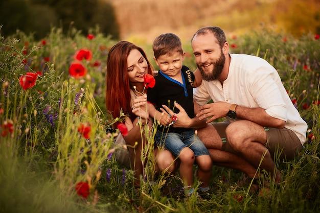 Vader en moeder houden hun zoontje op de armen staande op het groene veld met klaprozen