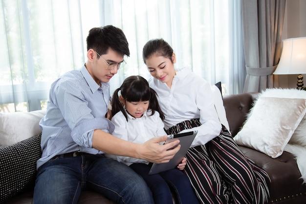 Vader en moeder kinderen leren tablet te gebruiken om hun huiswerk thuis te maken aziatische familie is blij