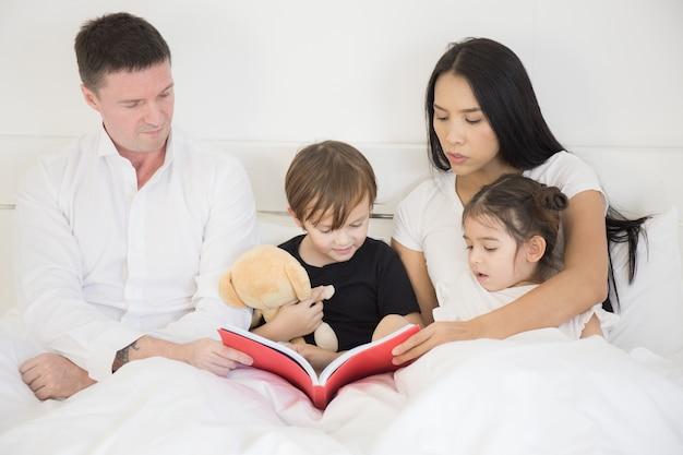 Vader en moeder leren hun kinderen op een wit bed