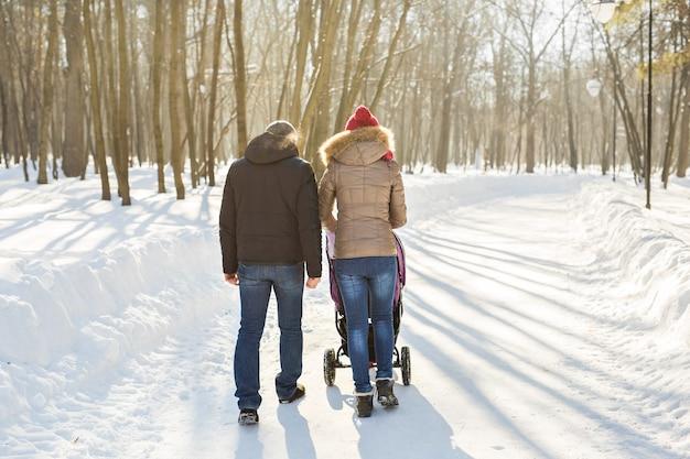 Vader en moeder met kinderwagen in winterbos.