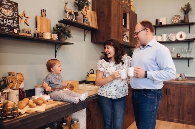 Vader en moeder met theekopjes lachen om hun zoon zittend op het aanrecht met houten lepel en glimlachen. keuken ingericht voor kerstmis.
