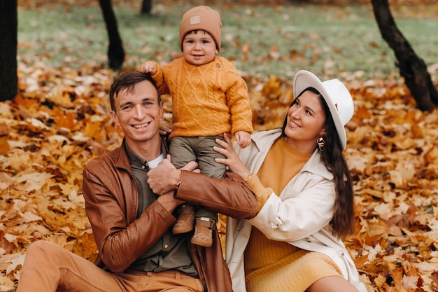 Vader en moeder met zoon wandelen in het najaar park. een gezin wandelt in de gouden herfst in een natuurpark.