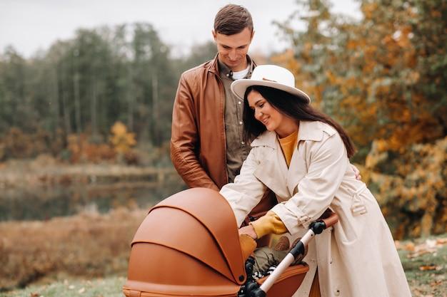 Vader en moeder op een wandeling met een kinderwagen in het herfstpark