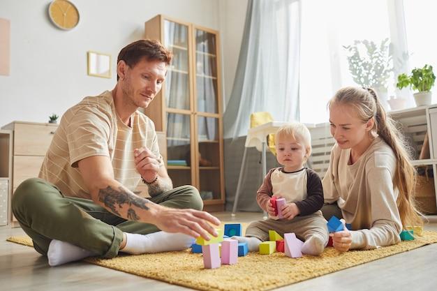 Vader en moeder spelen met zijn zoontje op de vloer in de woonkamer