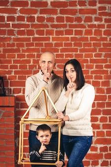 Vader en moeder tonen shh, en zoon toont shh van geïmproviseerd huis op een bakstenen muur