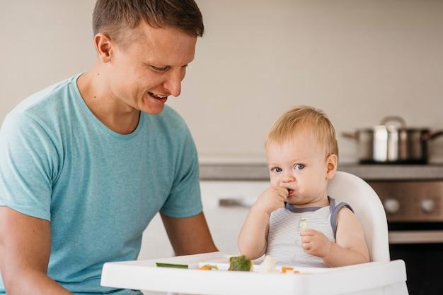 Vader en schattige baby in kinderstoel eten