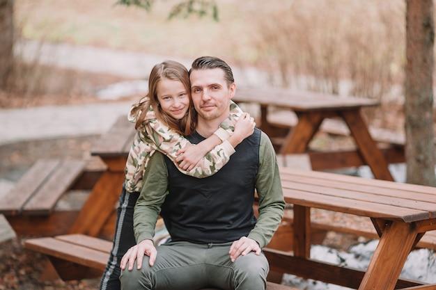 Vader en schattige dochters met hond buitenshuis