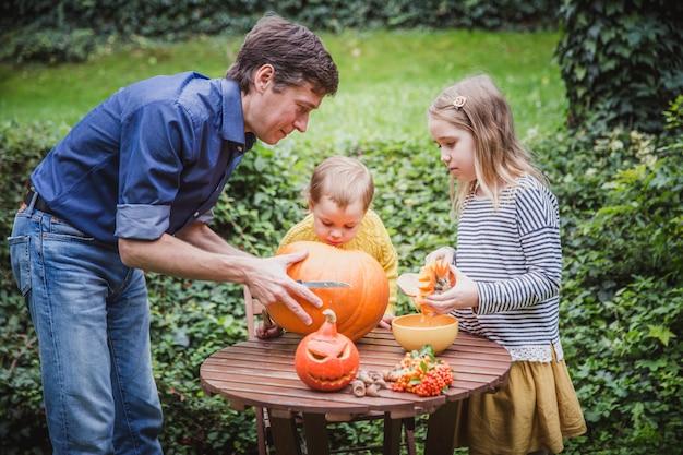 Vader en twee dochter snijdende pompoen voor halloween