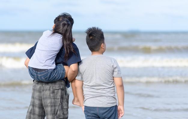 Vader en twee kinderen lopen op strand,