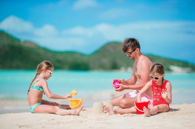 Vader en twee meisjes die met zand op tropisch strand spelen