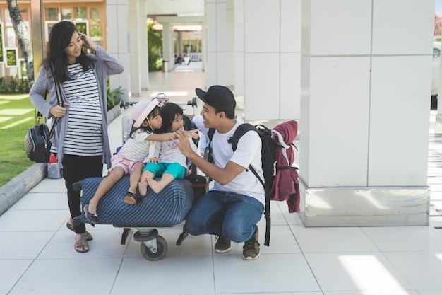 Vader en twee van haar dochter praten graag en moeder staat naast een trolley