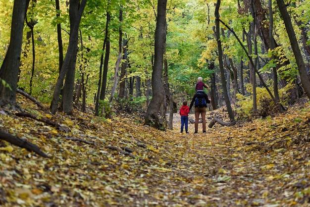Vader en twee zonen wandelen in het herfstbos. jongere zoon zit op de schouders van zijn vader. achteraanzicht