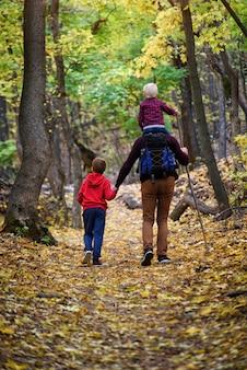 Vader en twee zonen wandelen in het herfstbos. jongere zoon zittend op de schouders van zijn vader. achteraanzicht