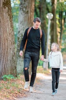 Vader en zijn aanbiddelijke kleine dochter in openlucht op zonnige de herfstdag