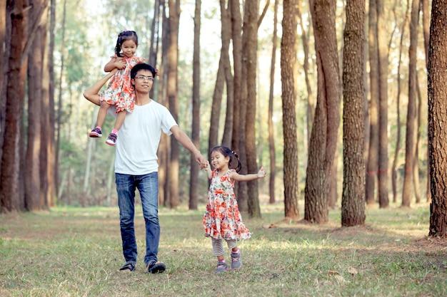 Vader en zijn dochters hebben plezier in het park spelen