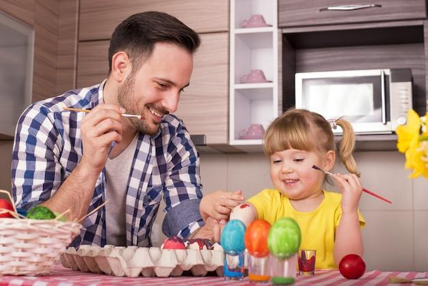 Vader en zijn kleine kind die de paaseieren schilderen