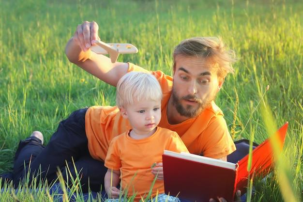 Vader en zijn peuterzoon lezen boek over vliegtuigen en reizen. authentiek levensstijlbeeld