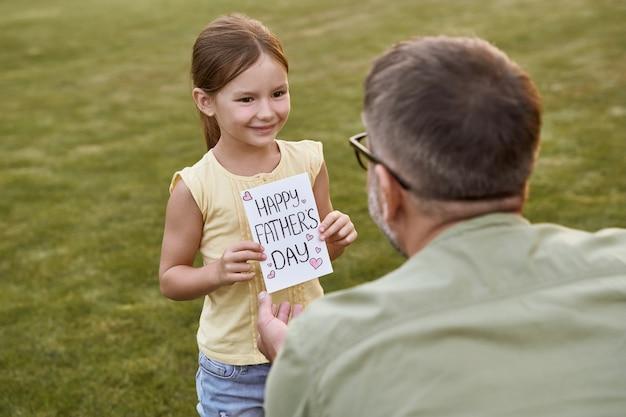 Vader en zijn schattige dochtertje vieren gelukkige vaderdag in het park op een warme dag klein meisje