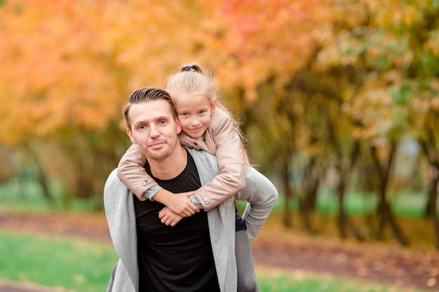 Vader en zijn schattige kleine dochter buitenshuis op zonnige herfstdag