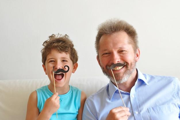 Vader en zijn schattige zoontje zetten een papieren baard op en glimlachen happy fathers day