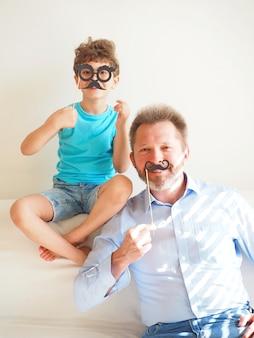 Vader en zijn schattige zoontje zetten papieren bril en snorren op en glimlachen. 1 april achtergrond.