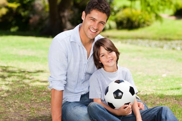 Vader en zijn zoon met hun bal in het park