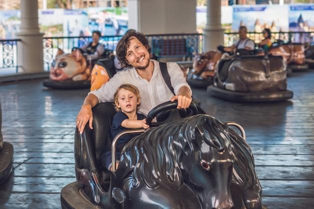 Vader en zijn zoon rijden in de botsauto bij het pretpark.