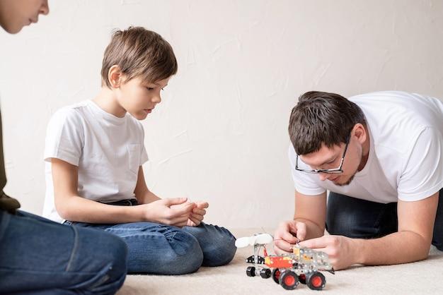 Vader en zijn zoons brengen samen tijd door en hebben plezier met het bouwen van robotauto's thuis zittend op het tapijt