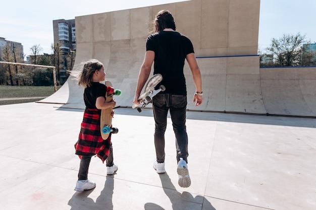Vader en zijn zoontje gekleed in de stijlvolle vrijetijdskleding lopen met de skateboards in hun handen in een skatepark op de zonnige dag.