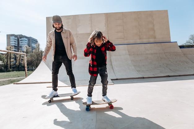 Vader en zijn zoontje gekleed in de vrijetijdskleding rijden skateboards in een skatepark met glijbanen buiten op de zonnige dag.