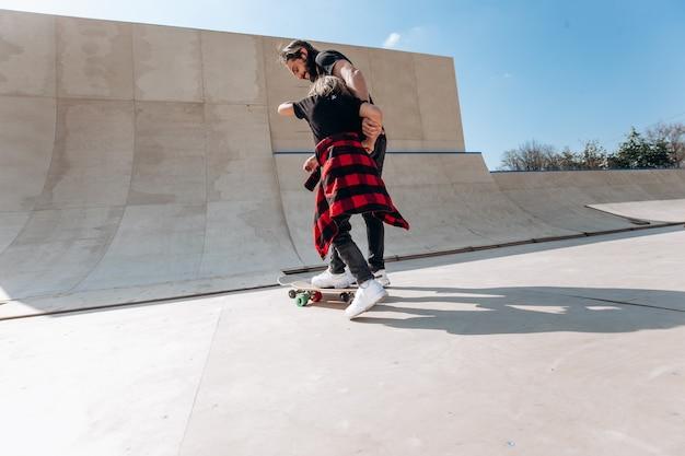 Vader en zijn zoontje gekleed in de vrijetijdskleding rijden skateboards in een skatepark met glijbanen op de zonnige dag.