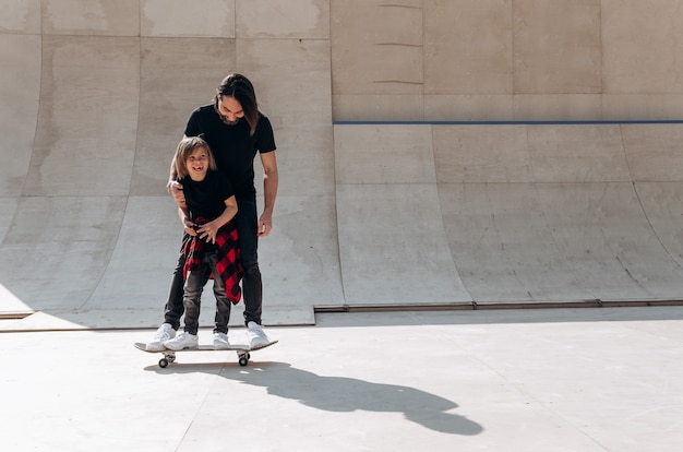 Vader en zijn zoontje gekleed in de vrijetijdskleding staan samen op het ene skateboard in een skatepark op de zonnige dag.