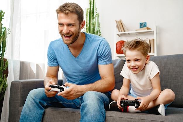 Vader en zijn zoontje spelen thuis samen videospelletjes