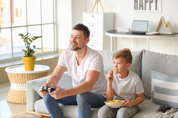Vader en zijn zoontje spelen thuis videogames
