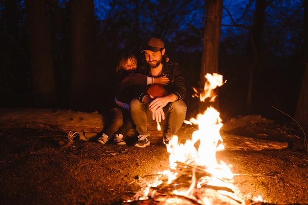 Vader en zijn zoontje zitten 's nachts samen op de houtblokken voor een vuur. de wandeling in het bos. .