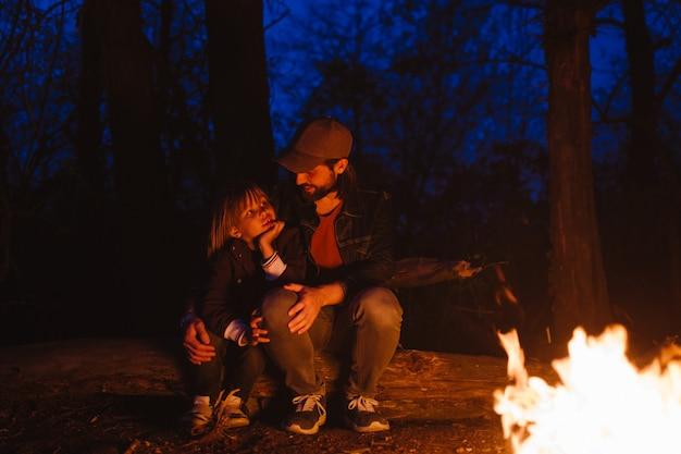 Vader en zijn zoontje zitten samen op de boomstammen voor een vuur tijdens een wandeling in het bos 's nachts. .