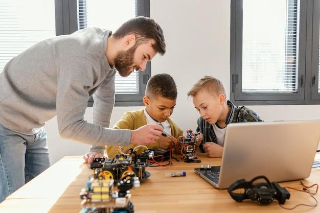 Vader en zonen die robot maken