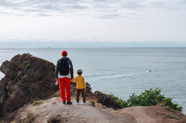 Vader en zonen genieten van de wind en kijken naar de zwarte zee terwijl ze bovenop de klif staan. fiolent, krim