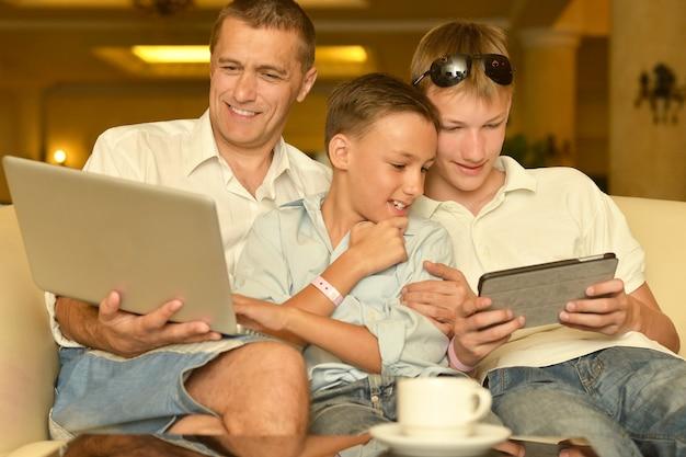 Vader en zonen met laptop aan tafel