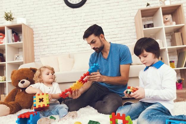 Vader en zonen speelt met speelgoed.