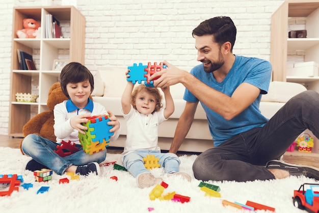 Vader en zonen spelen met speelgoed.